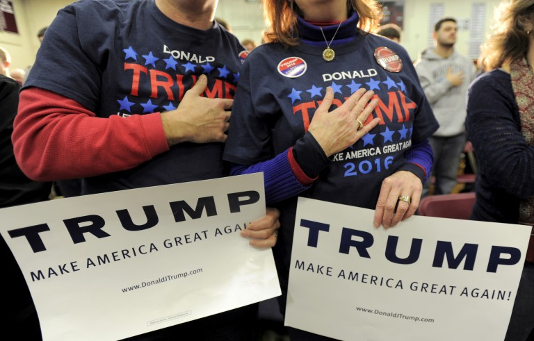 Supporters of U.S. Republican presidential candidate Donald Trump hold their hands to their chest as the national anthem is played at a campaign rally in Concord, New Hampshire January 18, 2016.      REUTERS/Gretchen Ertl/File photo - RTX2CWBE