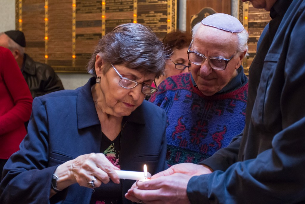 Sol and TKTKTKT light a candle in rememberance of the victims of the Holocaust during the Yom HaShoah rememberance at the Kehila Kedosha Janina in New York City on May 1, 2016.