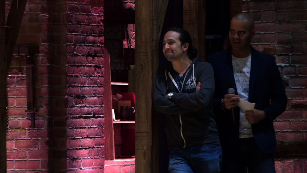 """Hamilton"" start Lin-Manuel Miranda and Christopher Jackson watch as New York City high school students perform short skits on the Broadway stage. PBS NewsHour"