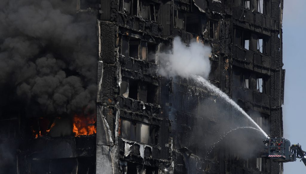 Firefighters direct jets of water onto a tower block severely damaged by a serious fire in north Kensington, West London on June 14. Photo by Toby Melville/Reuters