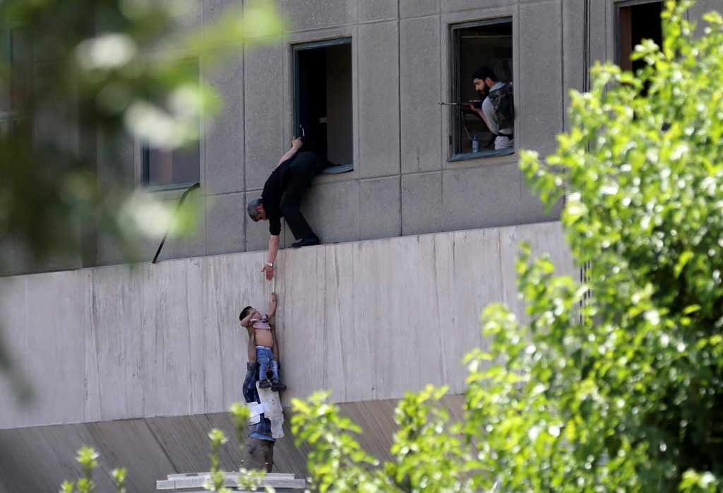 A boy is evacuated during an attack on the Iranian parliament in central Tehran on June 7. Photo by Omid Vahabzadeh/TIMA via Reuters