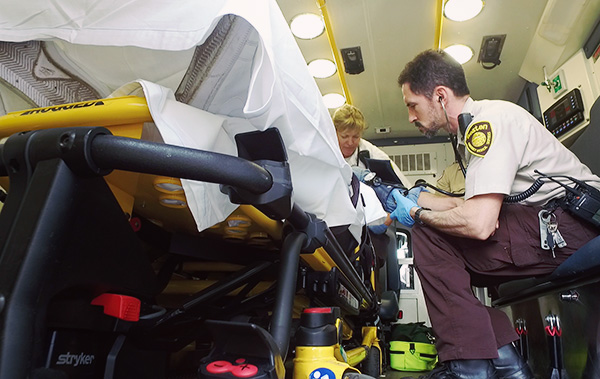 An EMT treats a patient in an ambulance