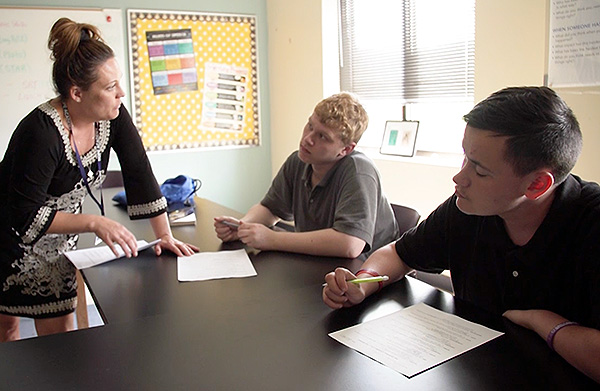 A high school teacher talks to students in a recovery school