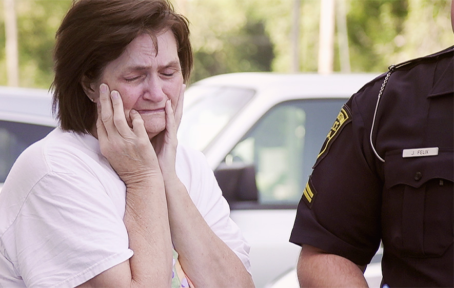 Woman cries next to a police officer