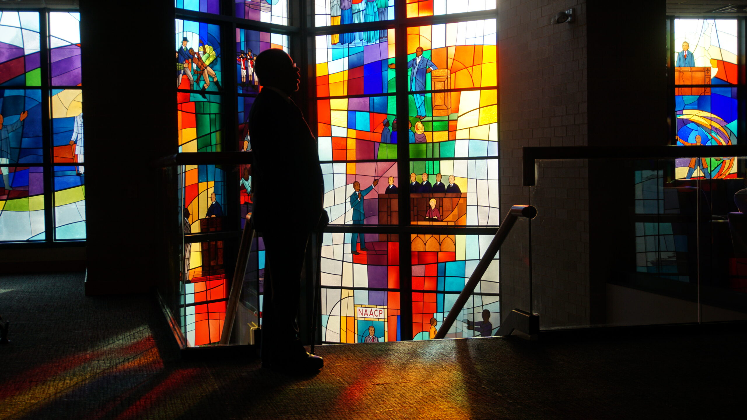 Host, Henry Louis Gates Jr. standing in front of stained glass