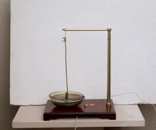 A copper wire hanging over a magnet that rests on a base.