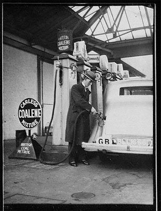 1935: A man filling his car at a station