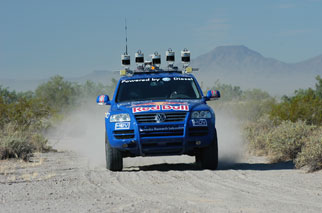 The modified VW Touareg kicking up dust on a desert road