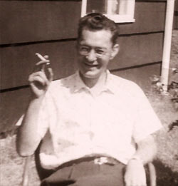 H.M. sitting outside, smoking a cigarette and smiling