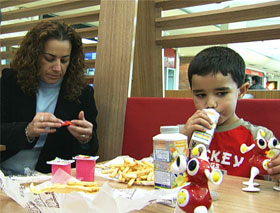 A woman and young boy eating a fast-food meal.