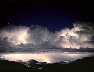 A thunderstorm over mountains, with stars visible above the clouds