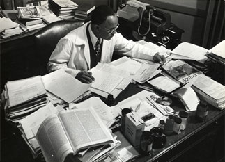 Julian at his desk covered in book and papers