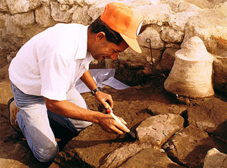 An excavator clearing a hearth with an ancient bread mold in the background