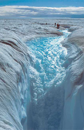 A waterfall surrounded by ice, the result of the melting of the Greenland ice cap