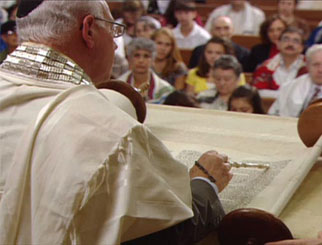 A rabbi reading from the Torah.