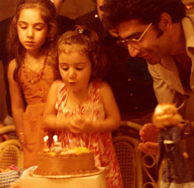 Young Sabeti blowing out candles on birthday cake
