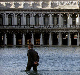 man knee-deep in water in Venice
