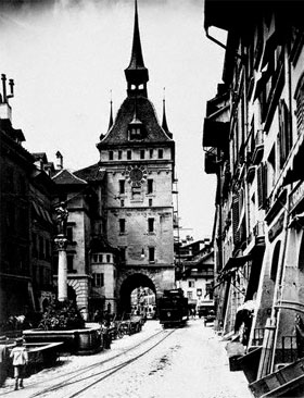 Old black-and-white photo of a streetcar driving near the clock tower in Bern