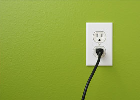 A black cord plugged into a white socket on a bright green wall