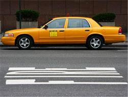 A taxi standing at a city curb.