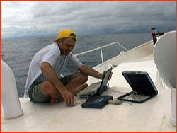 Mark attempting to transmit, via laptop and satphone, from deck of Orca