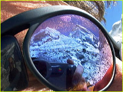 Closeup of sunglasses with mountain in reflection