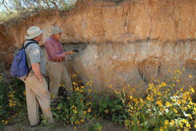 Vance Haynes points out layer of dark soil to geophysicist Allen West