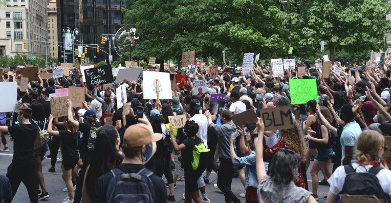 Black Lives Matter protestors walk with signs