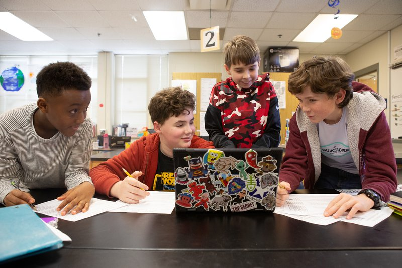 Four sixth-grade male students researching a science project on a laptop