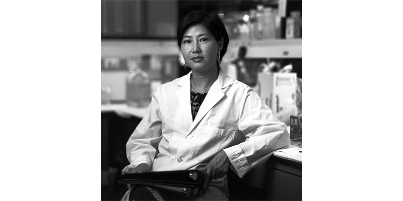 Black and white photo of Flossie Wong-Staal in a lab coat at the National Cancer Institute