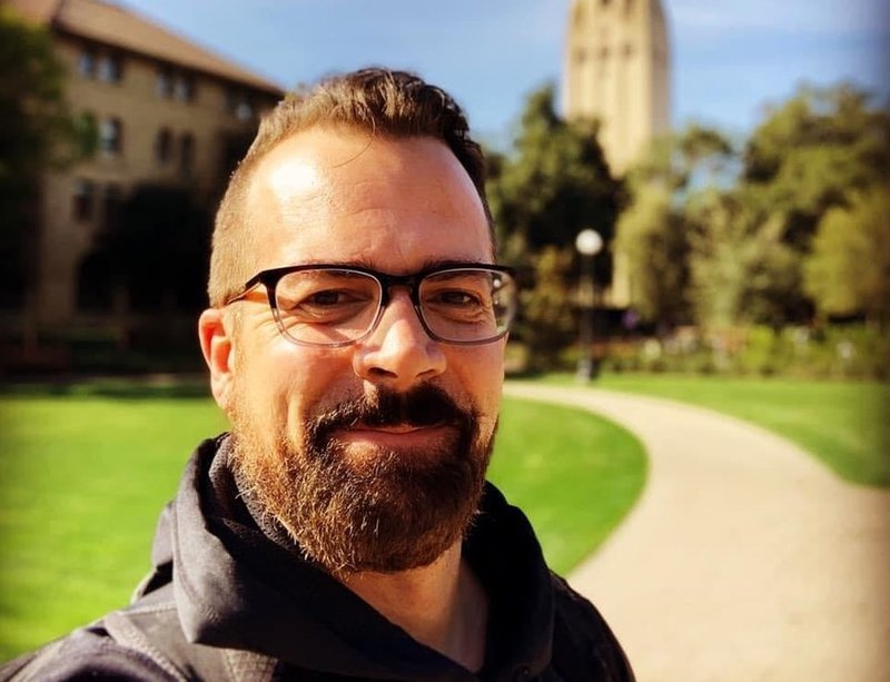 Man's face, smiling, on a campus