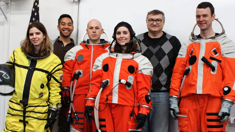 Space suit designers standing with people in space suits