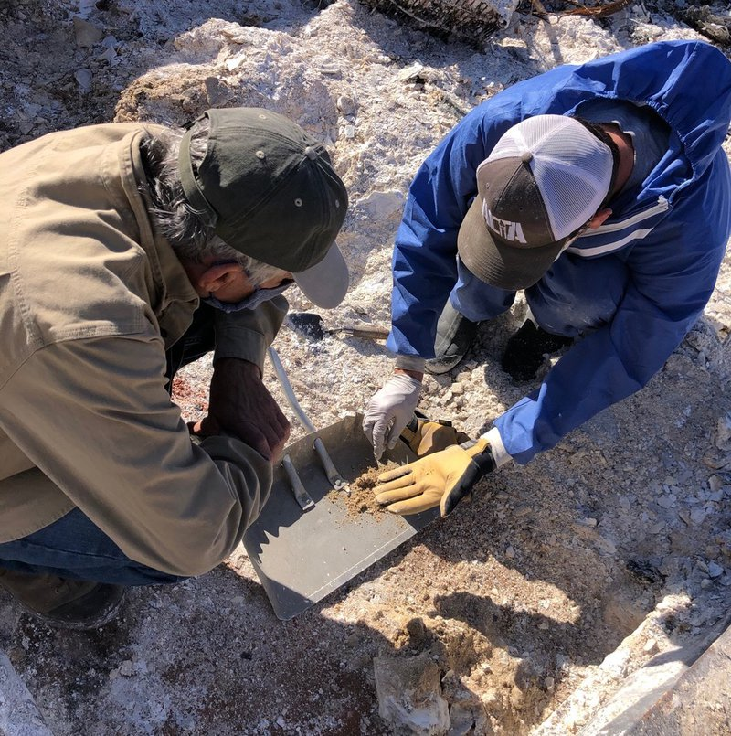 Two men look at ashes in dust pan
