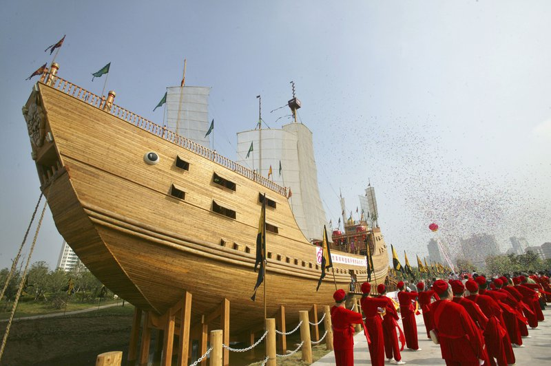 Performers next to large wooden ship in city