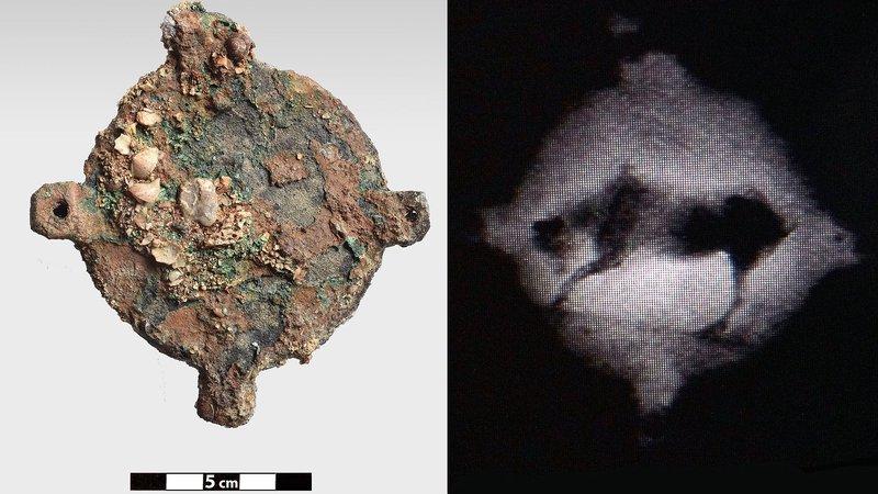 Χάλκινο δισκοειδές αντικείμενο, με τέσσερις διάτρητες αποφύσεις, πάνω στο οποίο, όπως έδειξε η ραδιογραφία, υπάρχει παράσταση ζώου, πιθανόν βοοειδούς