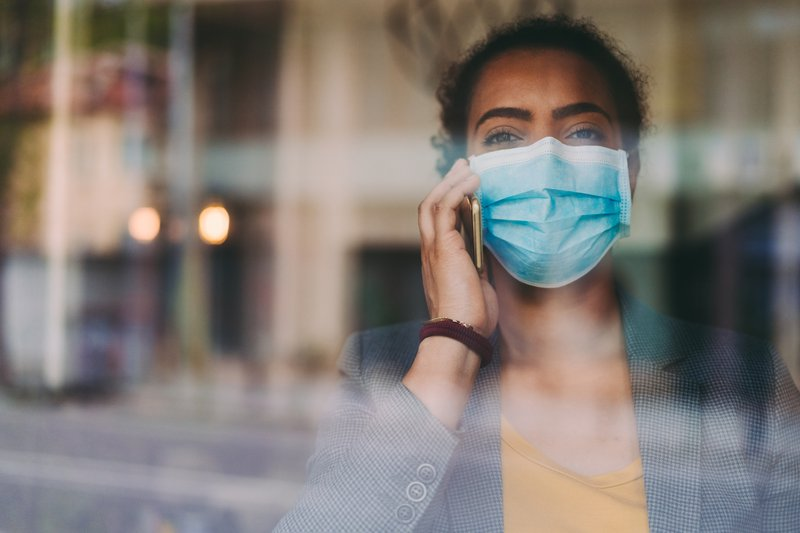 Person wearing surgical mask, talking on phone