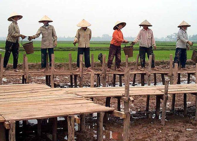 Vietnam villagers hauling buckets
