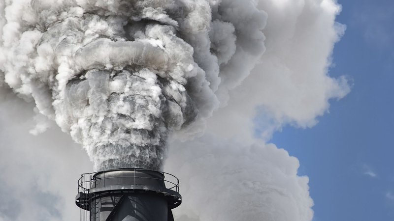 Smoke billowing out of industrial chimneys.