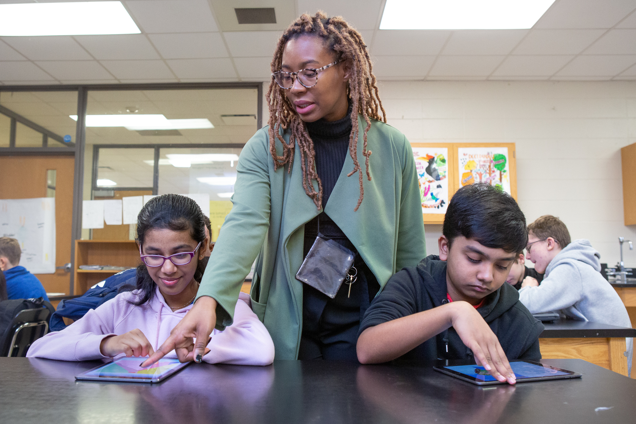 A teacher pointing out an image on a student's iPad