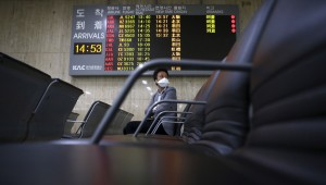A passenger wearing masks to prevent contracting Middle East Respiratory Syndrome (MERS) sits in front of an arrivals signboard at Gimpo International Airport in Seoul, South Korea, June 17, 2015.