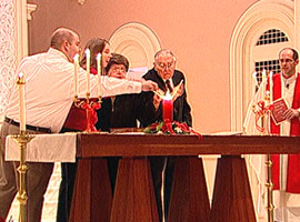 The longest-married couple and newest married couple light the unity candle together at the Mass for Lovers