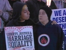 Couple holding marriage equality poster