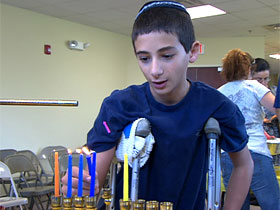 Lighting a menorah in Rabbi Bukiet's Hanukkah workshop