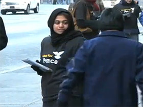 An Ahmadiyya Muslim volunteer hands out flyers in Times Square