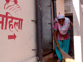 Mamta Bidlan cleaning around a public toilet facility for women